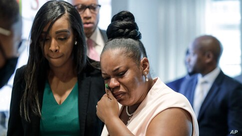 Tomika Miller, right, widow of Rayshard Brooks, who was shot fatally by police officer Garrett Rolfe, cries as she leaves a news conference, June 17, 2020, in Atlanta, Georgia.