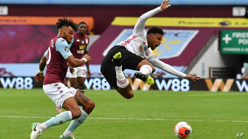 Sheffield United's Mbwana Samatta, right, is tackled by Aston Villa's Tyrone Mings during the English Premier League soccer match between Aston Villa and Sheffield United at Villa Park in Birmingham, England, June 17, 2020.