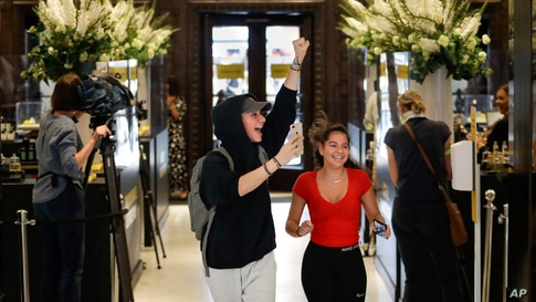 Customers cheer as they are allowed in the Selfridges department store in London.