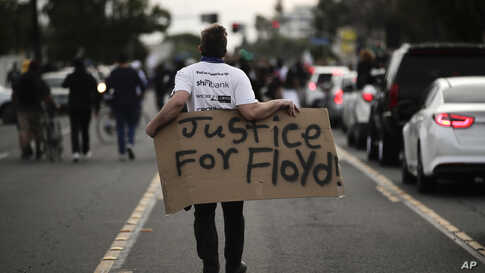 A demonstrator walks with a sign during a protest, June 1, 2020, in Anaheim, California, over the death of George Floyd in Minneapolis.