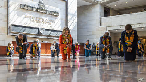 House Speaker Nancy Pelosi of Calif., center, and other members of Congress, kneel and observe a moment of silence at the Capitol's Emancipation Hall, on Capitol Hill in Washington,reading the names of George Floyd and others died during police interactions.
