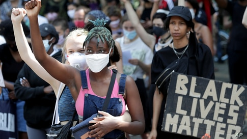 Young women take part in a Black Lives Matter anti-racism protest rally in Berlin, Germany, June 27, 2020.