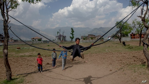A boy plays on a makeshift swing on a hot summer day on the outskirts of Srinagar, Indian controlled Kashmir.