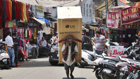 An Indian laborer talks on his mobile phone as he transports a refrigerator on his back at a market in Jammu.