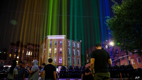 A rainbow light display illuminates the night sky in the West Village near The Stonewall Inn, birthplace of the gay rights movement, June 27, 2020, in New York.