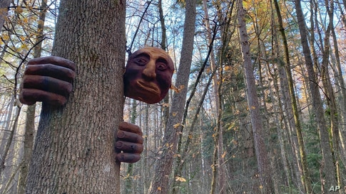 "A ""friendly giant"" sculpture hangs from a tree in the Hanmer Heritage Forest at Hammer Springs, New Zealand."
