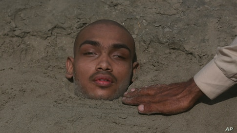 A Pakistani adjusts sand around an ailing child partially buried up to his neck at seaside during the partial solar eclipse in Karachi.