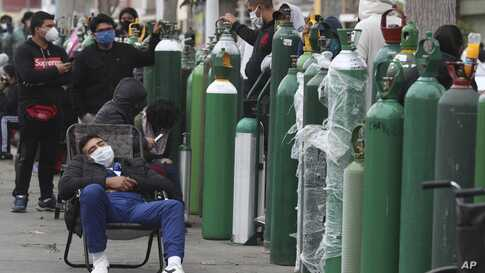 People wearing masks amid the spread of the new coronavirus wait for hours, some for 10 hours, to refill their oxygen cylinders at a shop in Callao, Peru, June 8, 2020.