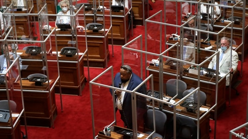 Rhode Island Democratic state Rep. Raymond Hull, below center, holds a microphone on the floor of the House Chamber separated by plastic protective barriers at the start of a legislative session,  June 17, 2020, at the Statehouse in Providence.