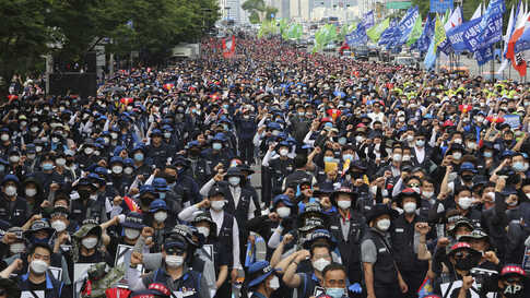 Workers wearing face masks to help protect against the spread of the new coronavirus stage a rally against the government's labor policy in Seoul, South Korea.
