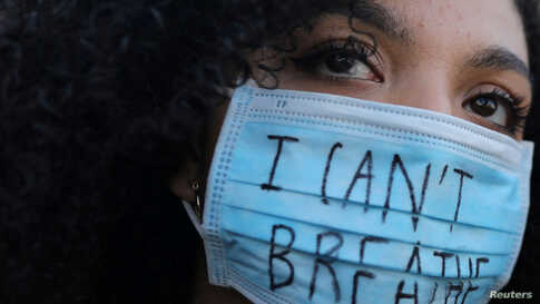 "A woman wearing a face mask with the words ""I can't breathe"" looks on during a protest in front of a U.S. consulate in Barcelona, Spain, June 1, 2020, against the death in Minneapolis police custody of George Floyd."