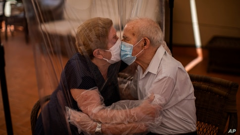 Agustina Cañamero, 81, and Pascual Pérez, 84, hug and kiss through a plastic film screen to avoid contracting the new coronavirus at a nursing home in Barcelona, Spain.