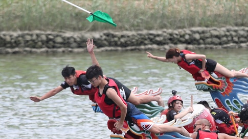 A boat leader reaches out to grab a finish line flag during the traditional Chinese dragon boat race in Taipei, Taiwan.