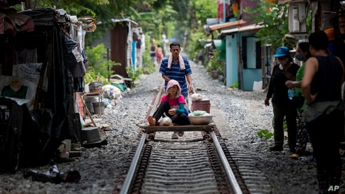 A vendor pushes a cart with a woman and merchandise along a rarely used rail track in Bangkok, Thailand.