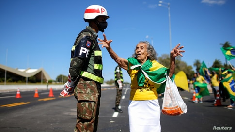 A supporter of Brazil's President Jair Bolsonaro talks with a soldier during a protest against the country's Supreme Federal Court, in front of the army headquarters in Brasilia.