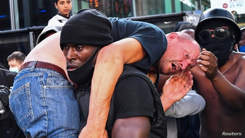 A protester carries an injured counter-protester to safety, near the Waterloo station during a Black Lives Matter protest in London, Britain, June 13, 2020.