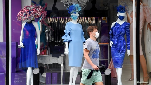 A man walks past a window display of a couture shop called Nataliya in Ascot, Britain, as racing resumes behind closed doors amid the outbreak of the COVID-19.