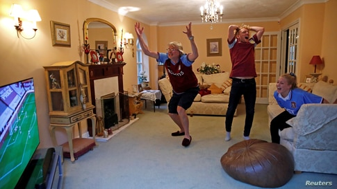 Aston Villa fans Martin, Harry and Lucy Chrispin watch the game on TV at home near Amersham, as the game resumes behind closed doors following the outbreak of the coronavirus disease (COVID-19).