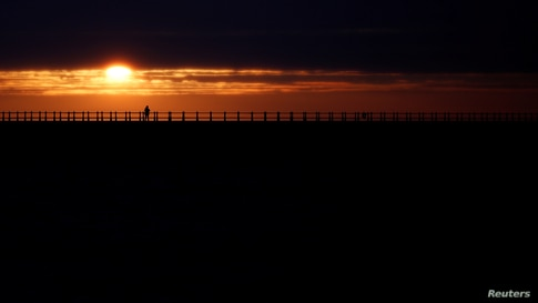 People look on as the sun rises during Summer Solstice, as seen from Roker Beach in Sunderland, Britain.