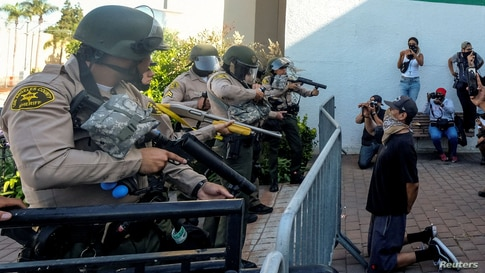 A demonstrator kneels as Los Angeles County sheriff's deputies prepare to fire pepper balls, flash-bangs and rubber bullets in a protest against the death of 18-year-old Andres Guardado and racial injustice, in Compton, California, June 21, 2020.