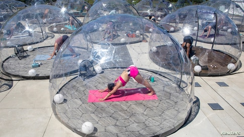 People participate in an outdoor yoga class by LMNTS Outdoor Studio, in a dome in Toronto, Ontario, Canada, June 21, 2020.