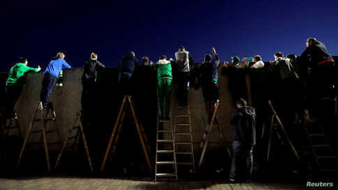 Fans standing on ladders behind a wall watch a match of the Czech top-tier soccer competition between Bohemians Prague and Sparta Prague as the match is closed for spectators due to the measures taken to curb the coronavirus disease (COVID-19) outbreak.