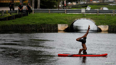 A man practices yoga on a paddle board outside Trump National Doral golf resort in Doral, Florida, June 6, 2020.
