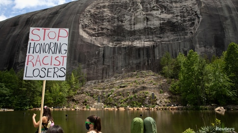 A protest sign is held up in front of the Confederate Monument carved into granite at Stone Mountain Park in Stone Mountain, Georgia, June 16, 2020.