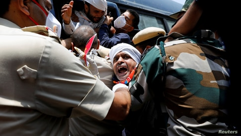 Police officers detain an activist from Swadeshi Jagran Manch, a wing of the Hindu nationalist organisation Rashtriya Swayamsevak Sangh (RSS), during a protest against China, in New Delhi, India.