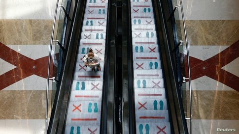 A woman wearing a protective face mask stands in an escalator with marks for social distancing during reopening at Pondok Indah Mall in Jakarta, Indonesia.