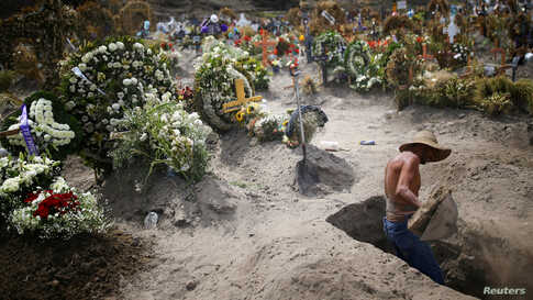 A cemetery worker dig a new grave at the Xico cemetery on the outskirts of Mexico City, as the coronavirus disease (COVID-19) outbreak continues, June 10, 2020.