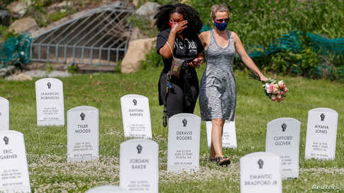 People walk among an art installation of headstones bearing the names of people killed by police near the site of the arrest of George Floyd, who died while in police custody, in Minneapolis, Minnesota, June 6, 2020.