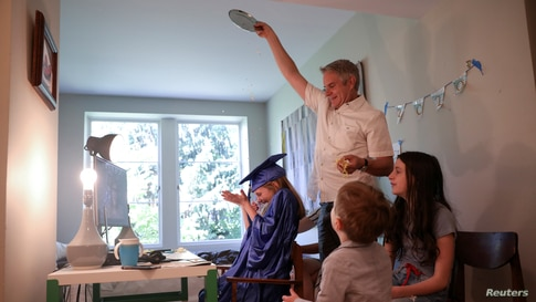 Doug Hassebroek pours confetti over his daughter Lydia, celebrating her graduation ceremony at home in Brooklyn, New York, June 17, 2020.