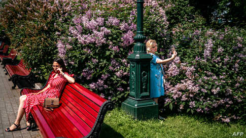 Women enjoy a warm and sunny day in a park in downtown Moscow on the first day after Russia lifted a range of anti-coronavirus measures.
