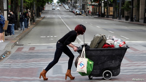 A woman pushes a cart during a protest against racial inequality and call for defunding of Seattle police, in Seattle downtown, Washington, June 14, 2020.