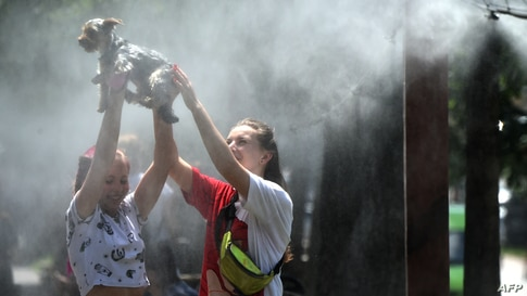 Girls refresh themselves and their dog with water spray frames set along the central street of the Ukrainian capital of Kyiv during a heatwave.