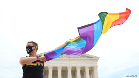 Joseph Fons holding a Pride Flag, stands in front of the U.S. Supreme Court building after the court ruled that a federal law banning workplace discrimination also covers sexual orientation, in Washington, D.C.