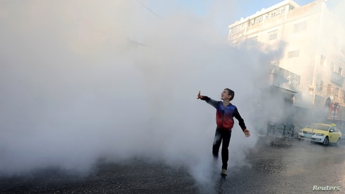 A Palestinian boy plays as disinfectants are sprayed by workers to sanitize cars and shops amid the coronavirus disease (COVID-19) outbreak in Hebron in the Israeli-occupied West Bank.