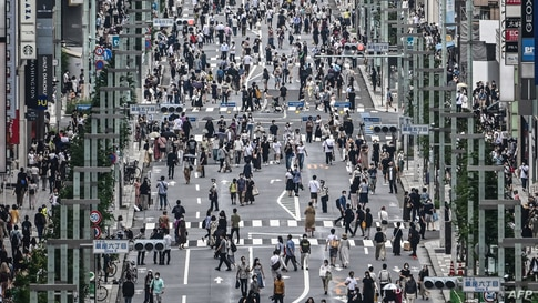 People walk on a street in Tokyo on July 24, 2020. - Some 260 new cases COVID-19 coronavirus infections were recorded in the…