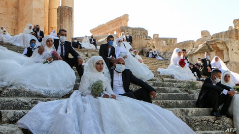 Lebanese couples, wearing protective face masks, sit on the steps during a group wedding at the Temple of Bacchus at the…