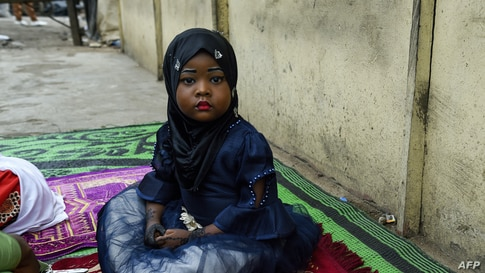 A young girl sits on a mat, as worshippers arrive to pray to mark the Muslim Eid-al-Adha (Festival of Sacrifices) without…