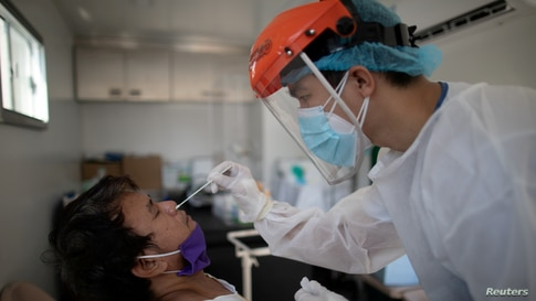 FILE PHOTO: FILE PHOTO: A nurse gets a swab from a man under observation for coronavirus disease (COVID-19) in a booth set up…