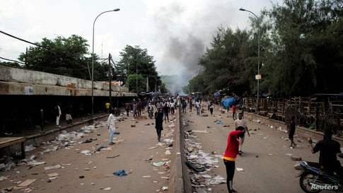 Smoke rises as supporters of Imam Mahmoud Dicko and other opposition political parties protest after President Ibrahim Boubacar…