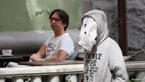 A man uses aplasticbagas a face mask as he walks past a cafe amid the coronavirusdisease (COVID-19) outbreak in Kyiv,…