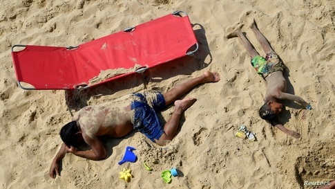 People enjoy the sunny weather at the Bournemouth Beach, amid the coronavirus disease (COVID-19) outbreak, in Bournemouth,…