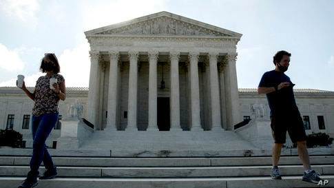 Two people walk down the steps outside the Supreme Court, July 9, 2020, in Washington.