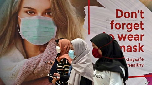 Women wearing protective face masks pass an advertisement promoting awareness of the coronavirus outbreak at a shopping mall in…