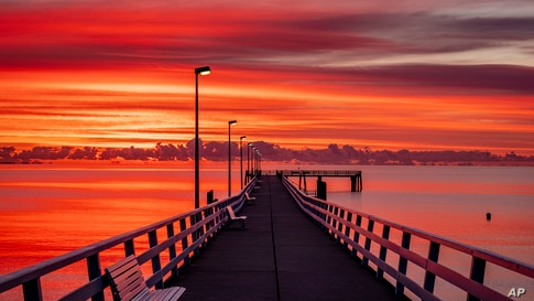 A pier is lit in the sunrise in Timmendorfer Strand at the Baltic Sea, northern Germany, Thursday, July 9, 2020. (AP Photo…