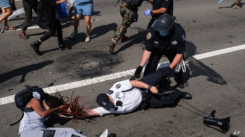 A Black Lives Matter protester and NYPD officers scuffle on the Brooklyn Bridge during a demonstration, Wednesday, July 15,…