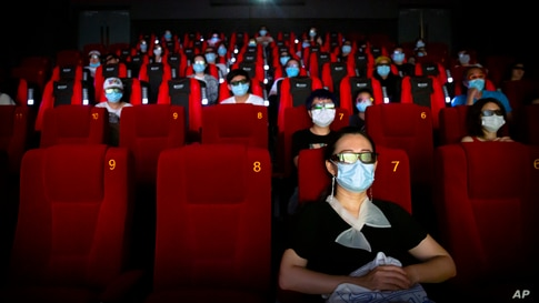 "People wearing face masks to protect against the coronavirus sit spaced apart as they watch the film ""Dolittle"" at a movie…"